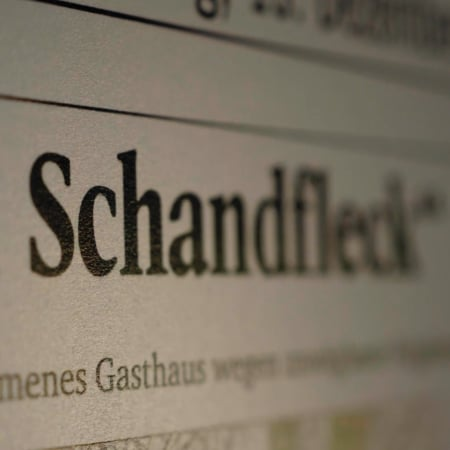 "Newspaper headline with the german word ""Schandfleck"" in focus"