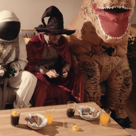 An astronaut a witch and a dinosaur sitting on a couch playing a game